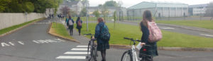Ursuline College pupils pushing bicycles up to the school