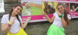 Girls pointing to Honk Production Sign outside Hawkswell